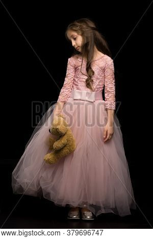 Cute Girl Posing With Teddy Bear, Charming Long Haired Girl Wearing Nice Pink Dress Looking Seriousl