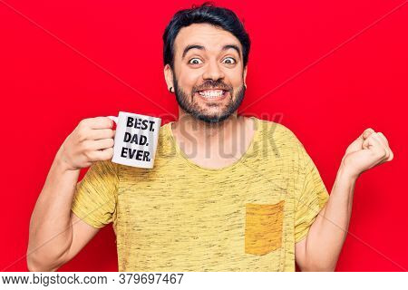 Young hispanic man drinking mug of coffe with best dad ever message screaming proud, celebrating victory and success very excited with raised arm