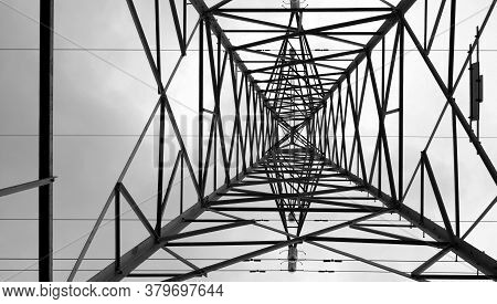 Symmetrical And Abstract Lines Of Electricity Pole Bottom-up Perspective In Black And White.