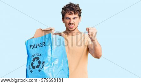 Young handsome man with curly hair holding recycling wastebasket with paper and cardboard annoyed and frustrated shouting with anger, yelling crazy with anger and hand raised