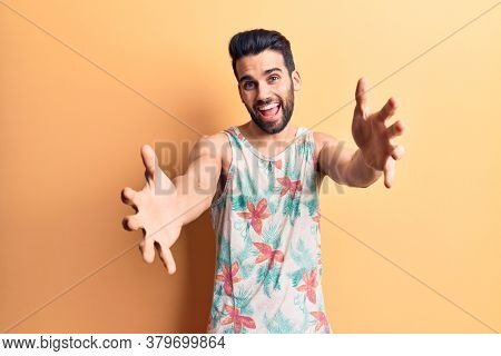 Young handsome man with beard wearing summer sleeveless t-shirt looking at the camera smiling with open arms for hug. cheerful expression embracing happiness.