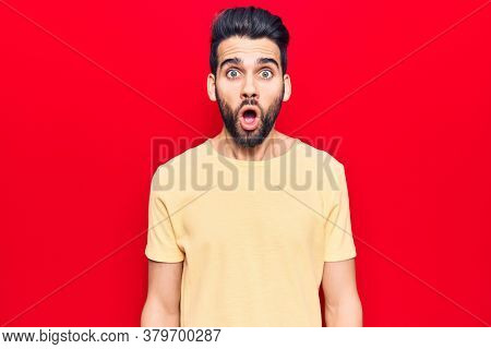 Young handsome man with beard wearing casual t-shirt scared and amazed with open mouth for surprise, disbelief face