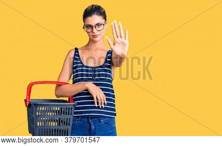 Young beautiful woman holding supermarket shopping basket with open hand doing stop sign with serious and confident expression, defense gesture
