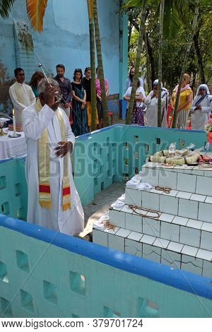 KUMROKHALI, INDIA - FEBRUARY 28, 2020: The priest blesses religious objects at the tomb of a Croatian missionary, Jesuit father Ante Gabric in Kumrokhali, West Bengal, India