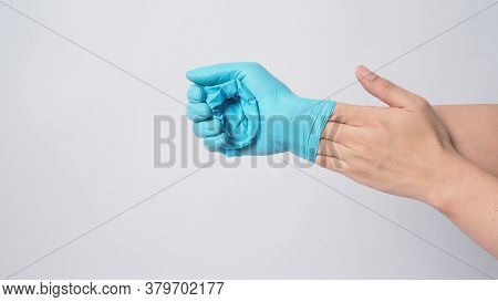 Hand Is Remove Blue Surgical Gloves By Putting The Fingers Inside The Glove On White Background.