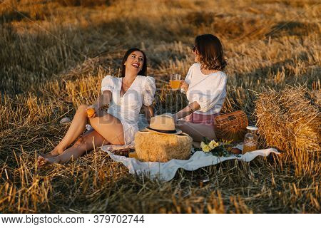 Two Girlfriends Lying On A Picnic Blanket And Smiling. Enjoying Time In Nature. Leisure And Free Tim