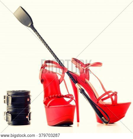 Bdsm Outfit For Adult Sex Games. Red High-heeled Striptease Shoes And Handcuffs, Whip Isolated On A
