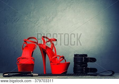 Bdsm Outfit For Adult Sex Games. Red High-heeled Striptease Shoes And Handcuffs, Whip On Dark Backgr