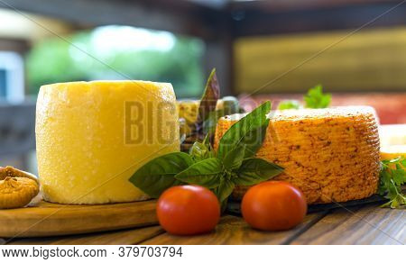 Cheese Heads With Cheeses Of Different Kinds. Assortment Of Different Cheese Types On Wooden Backgro