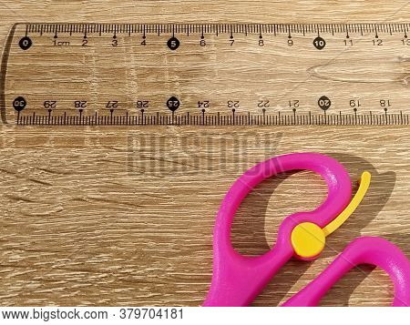Transparent Plastic School Ruler On A Wooden Table. Millimeters And Centimeters Are Marked In Black.