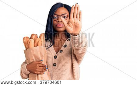 Young african american woman holding paper bag with bread with open hand doing stop sign with serious and confident expression, defense gesture