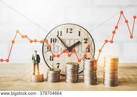Miniature Standing Business Man With Blurred Stack Of Coins And Analog Clock , Orange Graph For Busi