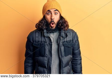 Young arab man wearing casual winter clothes scared and amazed with open mouth for surprise, disbelief face