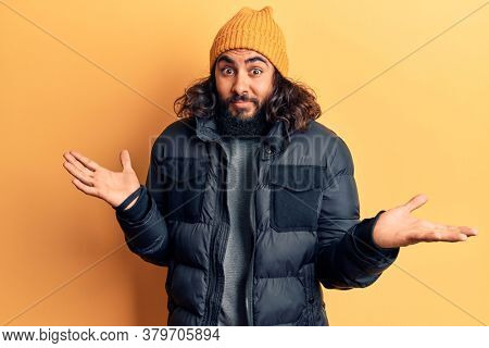Young arab man wearing casual winter clothes clueless and confused expression with arms and hands raised. doubt concept.