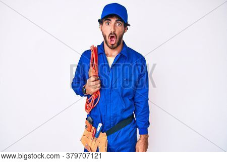 Handsome young man with curly hair and bear wearing builder jumpsuit uniform and electric cables scared and amazed with open mouth for surprise, disbelief face