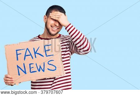 Young handsome man holding fake news message banner stressed and frustrated with hand on head, surprised and angry face