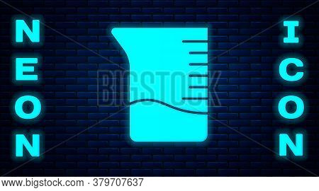 Glowing Neon Measuring Cup Icon Isolated On Brick Wall Background. Plastic Graduated Beaker With Han