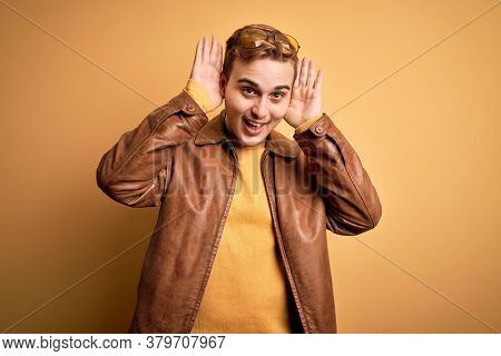 Young handsome redhead man wearing casual leather jacket over isolated yellow background Smiling cheerful playing peek a boo with hands showing face. Surprised and exited