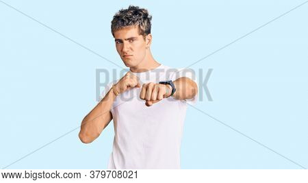 Young handsome man wearing casual white tshirt punching fist to fight, aggressive and angry attack, threat and violence