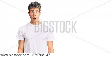 Young handsome man wearing casual white tshirt afraid and shocked with surprise and amazed expression, fear and excited face.