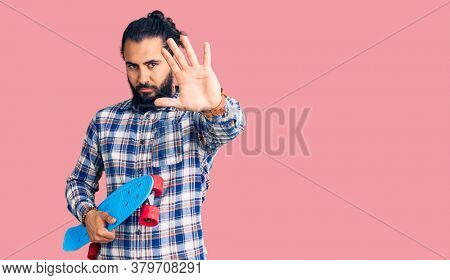 Young arab man holding skate with open hand doing stop sign with serious and confident expression, defense gesture