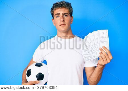 Young handsome man holding soccer ball and dollars banknotes clueless and confused expression. doubt concept.