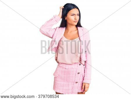 Young beautiful latin woman wearing business clothes confuse and wondering about question. uncertain with doubt, thinking with hand on head. pensive concept.