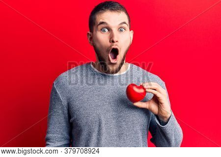 Young handsome man holding heart scared and amazed with open mouth for surprise, disbelief face