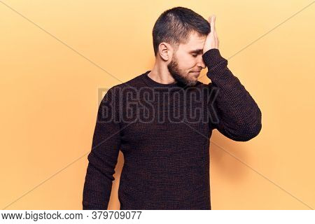 Young handsome man wearing casual sweater surprised with hand on head for mistake, remember error. forgot, bad memory concept.