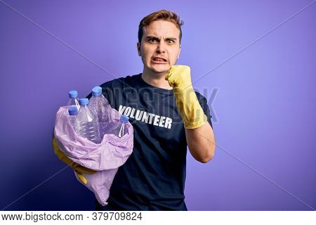 Young handsome redhead volunteer man doing volunteering holding bag with plastic bottles annoyed and frustrated shouting with anger, yelling crazy with anger and hand raised