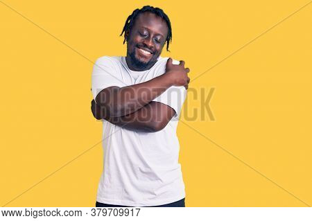 Young african american man with braids wearing casual white tshirt hugging oneself happy and positive, smiling confident. self love and self care