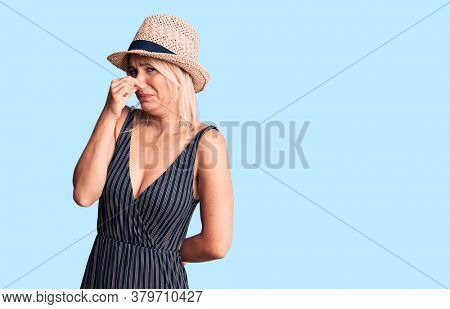 Young beautiful blonde woman wearing summer hat and dress smelling something stinky and disgusting, intolerable smell, holding breath with fingers on nose. bad smell