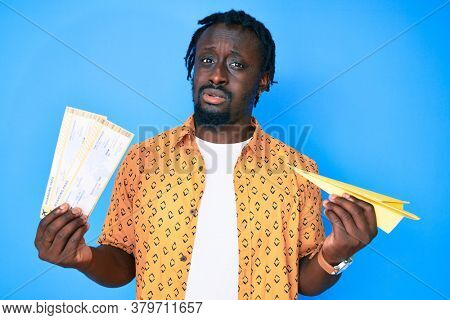 Young african american man with braids holding paper airplane and boarding pass clueless and confused expression. doubt concept.