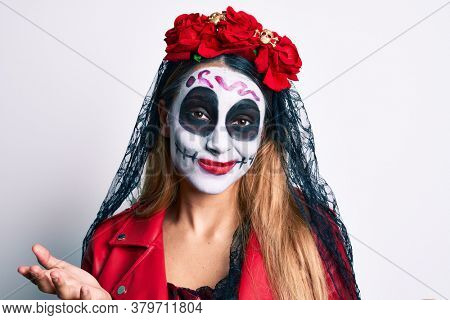 Woman wearing day of the dead costume over white clueless and confused expression with arms and hands raised. doubt concept.