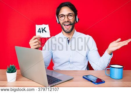 Handsome hispanic man working at the office holding 4k  banner celebrating achievement with happy smile and winner expression with raised hand