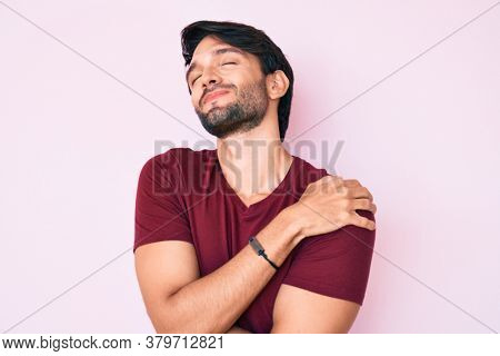 Handsome hispanic man wearing casual clothes hugging oneself happy and positive, smiling confident. self love and self care