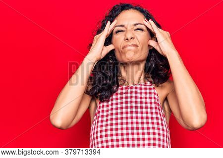 Middle age beautiful woman wearing casual sleeveless t shirt with hand on head, headache because stress. suffering migraine.