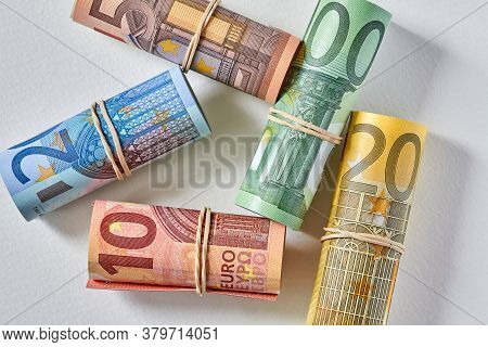 Ten, Twenty, Fifty And One And Two Hundred Euro Bill Rolled Up As A Tubule Lies On The Light Backgro