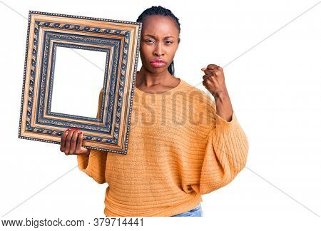 Young african american woman holding empty frame annoyed and frustrated shouting with anger, yelling crazy with anger and hand raised