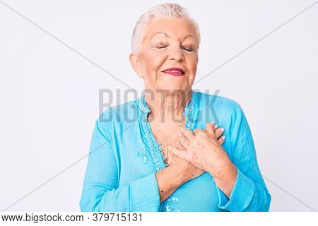 Senior beautiful woman with blue eyes and grey hair wearing summer clothes smiling with hands on chest, eyes closed with grateful gesture on face. health concept.