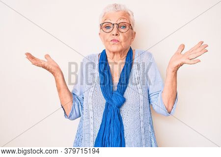 Senior beautiful woman with blue eyes and grey hair wearing casual sweater and scarf clueless and confused with open arms, no idea and doubtful face.