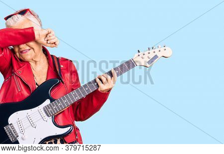 Senior beautiful woman with blue eyes and grey hair wearing a modern look playing electric guitar smiling cheerful playing peek a boo with hands showing face. surprised and exited