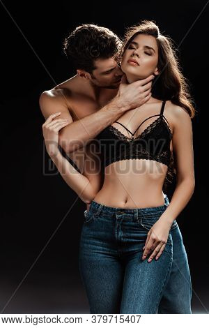 Handsome Man Kissing Neck Of Sensual Woman In Bra On Black