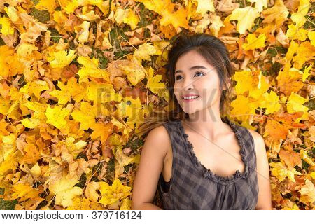 Young Happy Asian Woman Smiling And Thinking While Lying Down On Yellow Autumn Leaves