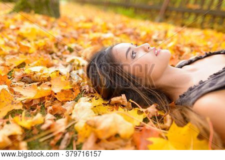 Focus Of Young Beautiful Asian Woman Looking Up While Lying Down On Yellow Autumn Leaves