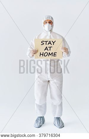Doctor In Protective Medical Suit Showing Blank Placard Stay At Home On White Background