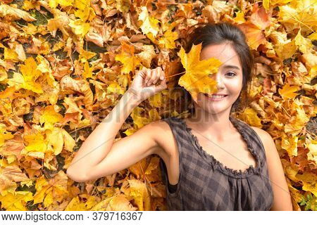 Young Happy Asian Woman Smiling While Covering Face With Leaf Lying Down On Yellow Autumn Leaves
