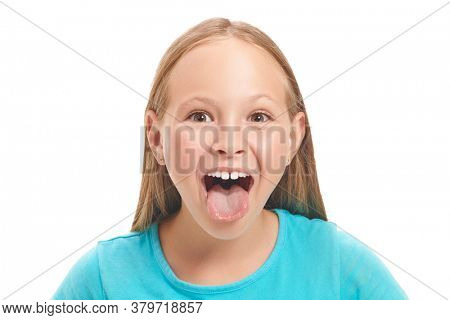 Emotional eight year old girl is teasing someone with his tongue out. Studio portrait on a white background. Copy space