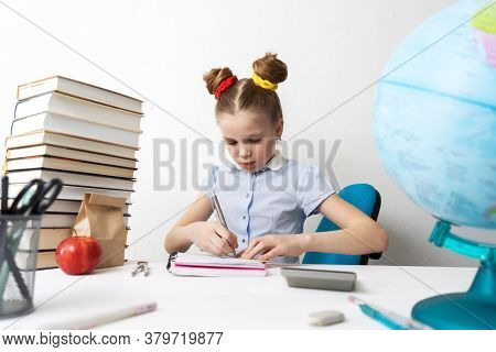 Back To School: A Girl Sits At Her Desk And Does Her Homework. Notebook Entries.
