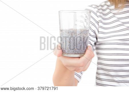 Hand Of Asian Woman Holding Glass Of Chia Seeds Soaking In Water Isolated On White Background. Free